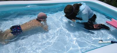 教師と子どもがビニールプールの中に入って、水に顔をつけている