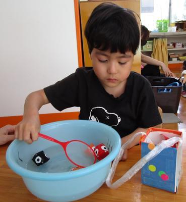 子どもが椅子に座って、洗面器の中に泳いでいる金魚をすくっている。。